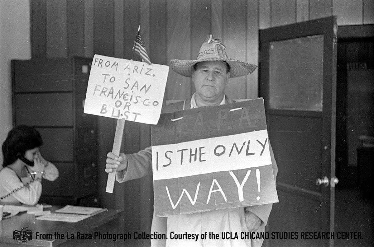 CSRC_LaRaza_B16F6S8_N001 Man holds sign | La Raza photograph collection. Courtesy of UCLA Chicano Studies Research Center