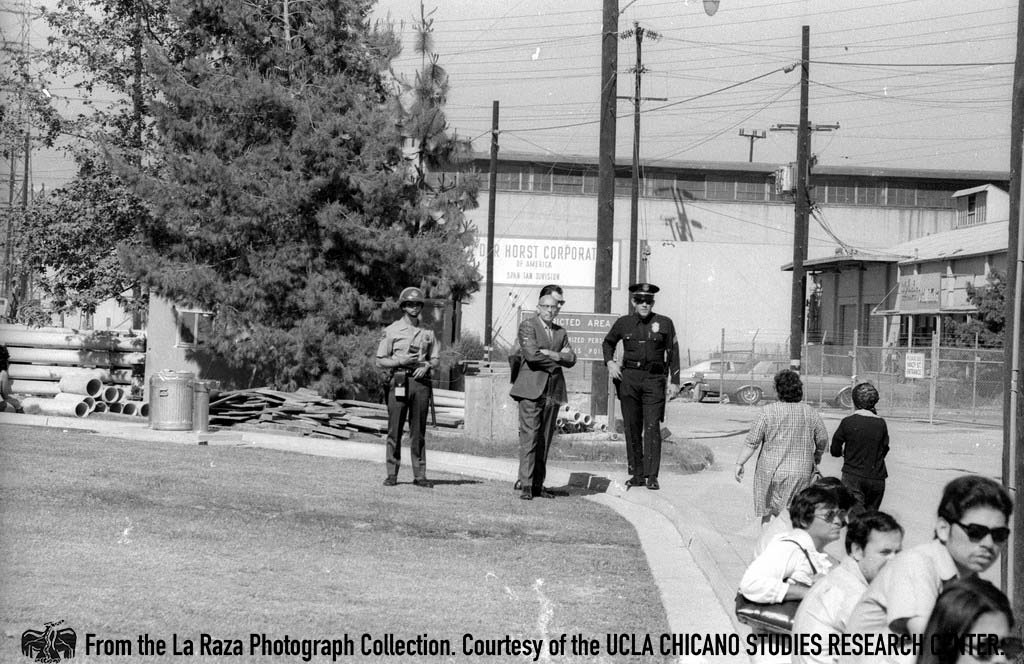 CSRC_LaRaza_B16F7S1_N048 LAPD officers watch protesters demonstrating in support of Ricardo Chavez Ortiz at L.A. County Jail | La Raza photograph collection. Courtesy of UCLA Chicano Studies Research Center