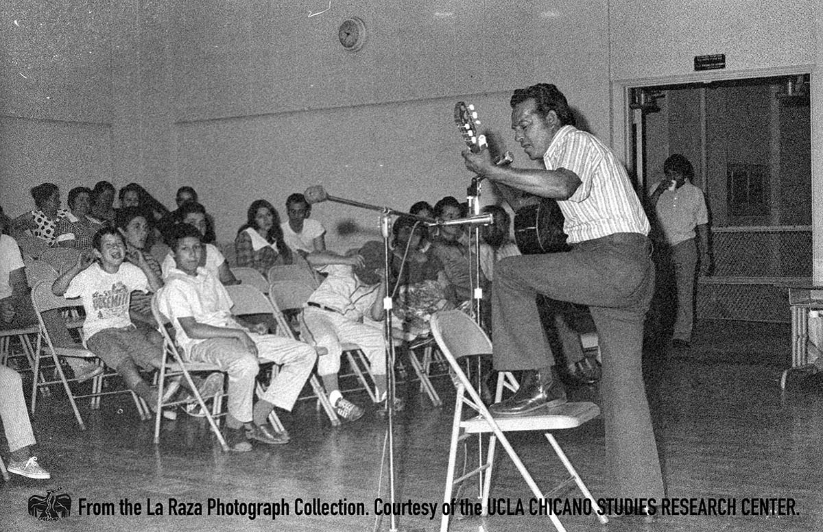 CSRC_LaRaza_B17F3S8_N017 Man plays guitar during La Raza Unida community meeting | Manuel Barrera, Jr., La Raza photograph collection. Courtesy of UCLA Chicano Studies Research Center