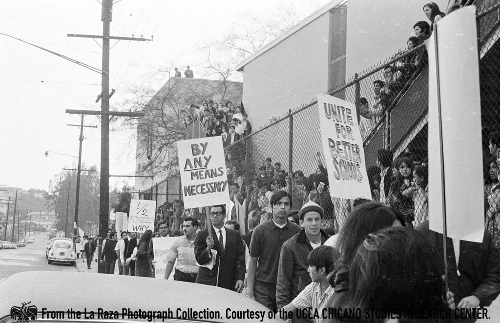 "CSRC_LaRaza_B1F3C3_DW_020 Man holds a ""by any means necessary"" poster at Roosevelt Walkouts 