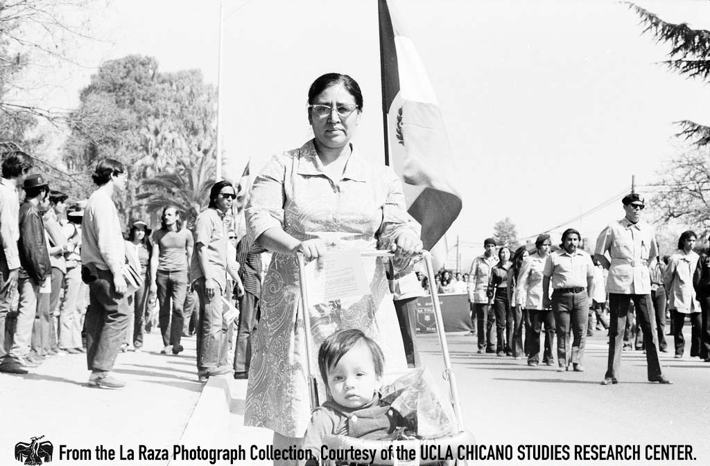 CSRC_LaRaza_B5F3C2_DZ_029 Women pushing stroller and carrying the Mexican flag at Fresno Moratorium | Daniel Zapata, La Raza photograph collection. Courtesy of UCLA Chicano Studies Research Center
