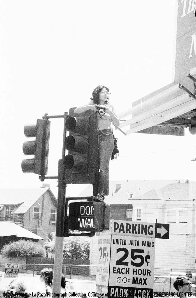 CSRC_LaRaza_B5F7C1_Staff_008 Maria Marquez Sanchez taking photos on top of a traffic light post at an anti-Vietnam War demonstration | La Raza photograph collection. Courtesy of UCLA Chicano Studies Research Center