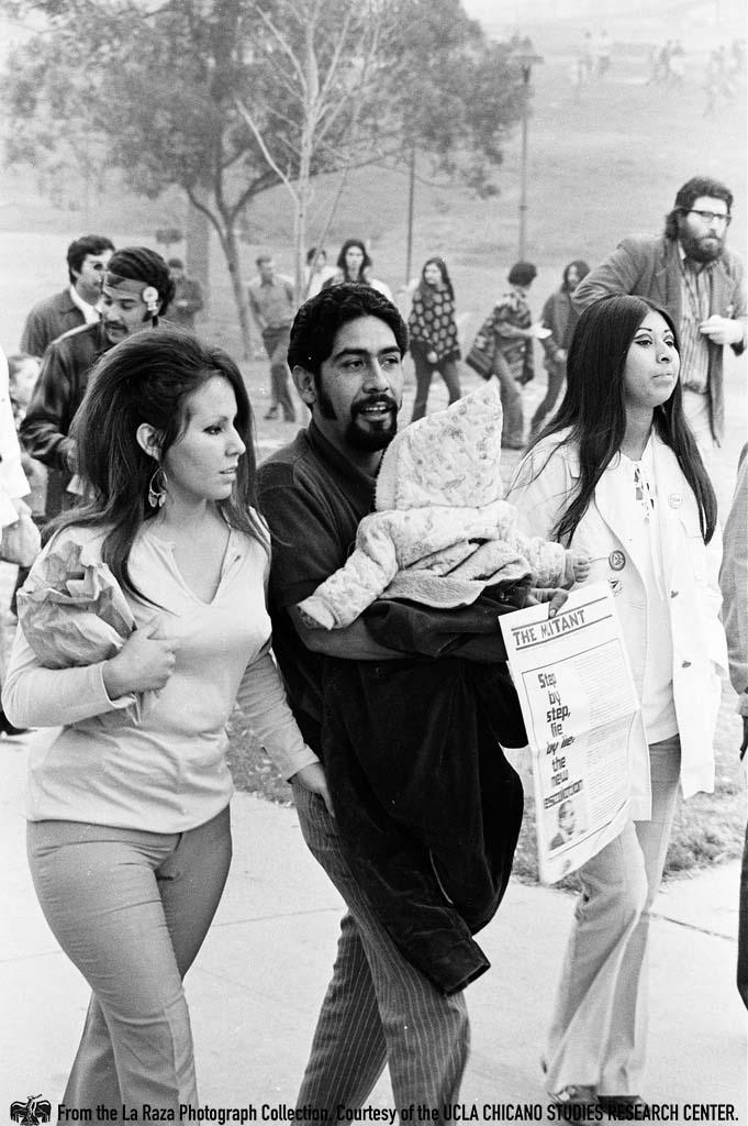 CSRC_LaRaza_B6F2aC3_OC_013 Man with baby at Marcha Por La Justicia Rally at Belvedere Park | Oscar Castillo, La Raza photograph collection. Courtesy of UCLA Chicano Studies Research Center