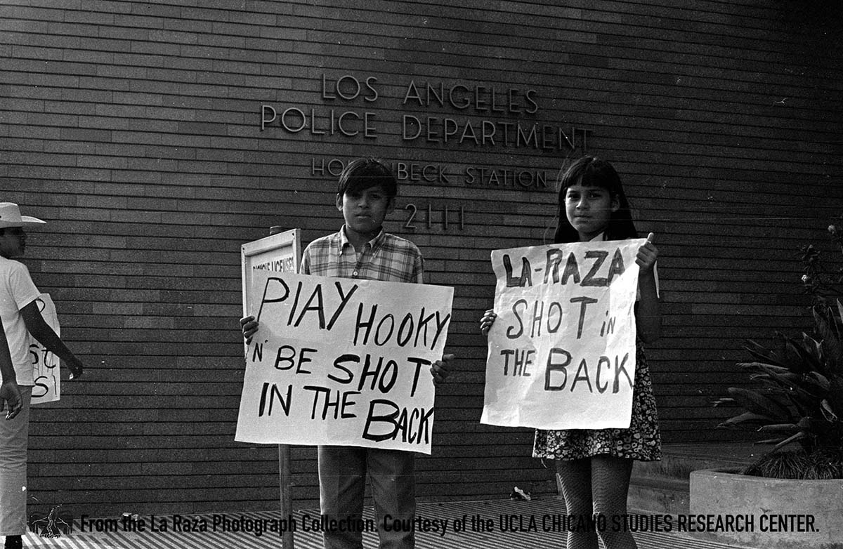 CSRC_LaRaza_B7F10S1_N018 Children holding signs at the demonstration against the death of Carlos Martinez in front of the LAPD Hollenbeck Police Station | La Raza photograph collection. Courtesy of UCLA Chicano Studies Research Center