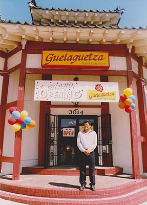 Fernando Lopez, Sr. standing in front of Guelaguetza at Grand Opening