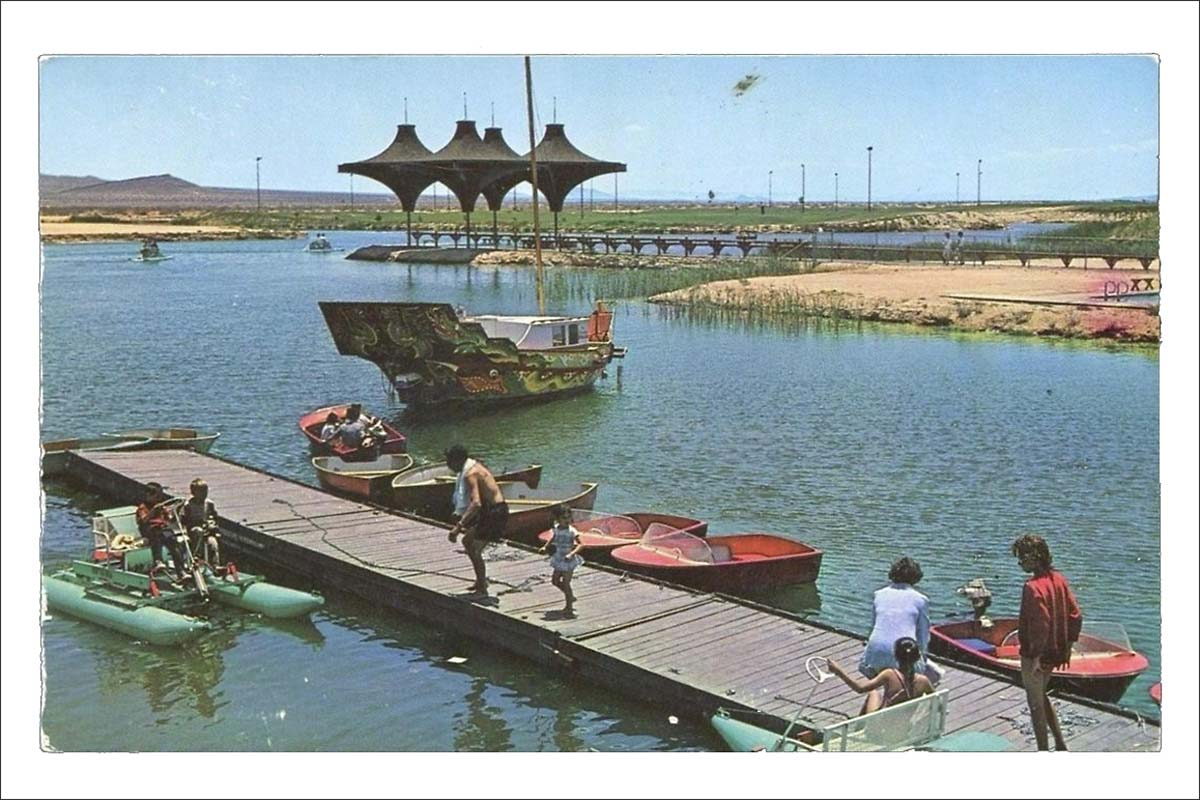 """A vintage postcard showing California City's newly constructed man-made lake with the signature geometric """"parasol"""" architectural flourishes on the pavilion that were incorporated in other city-designed structures."""