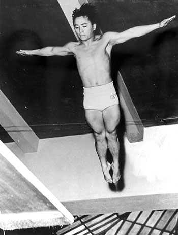 Sammy Lee, wearing Oxy trunks, dives