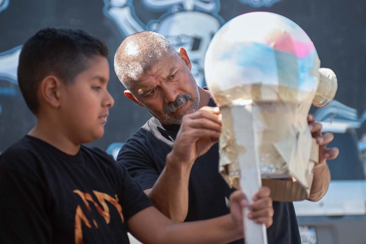 A young boy and a man work on a sculpture at Self Help Graphics' Dia de los Muertos season of workshops, 2019. | Ken Marchionno