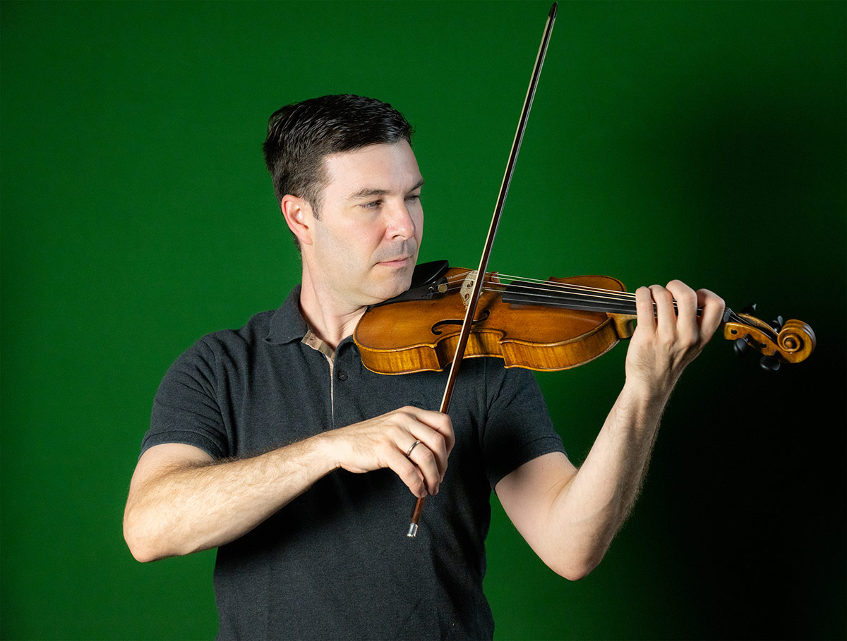 Nathan Cole plays the violin in front of a green wall. | Courtesy of Nathan Cole