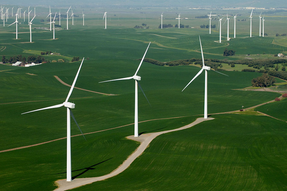 Aerial of Wind Turbines across Low Green Hills
