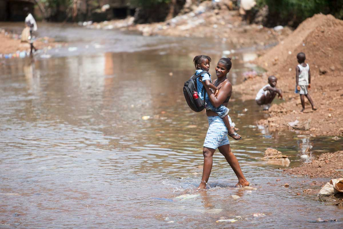 A woman carries a child across a river in Freetown, Sierra Leone.  | Nicky Milne/Thomson Reuters Foundation