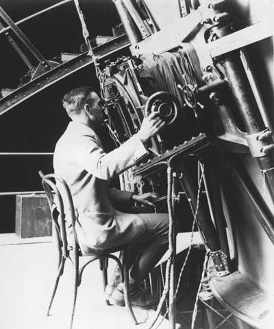 Edwin Powell Hubble seated at the Newtonian focus of the 100-inch telescope on Mount Wilson  |  Image courtesy of the Observatories of the Carnegie Institution for Science Collection at the Huntington Library, San Marino, California