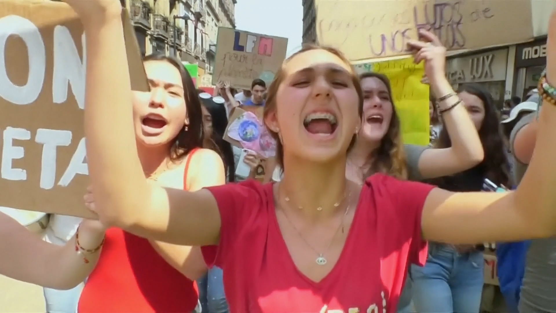 """Young people hold up signs at a climate protest. 