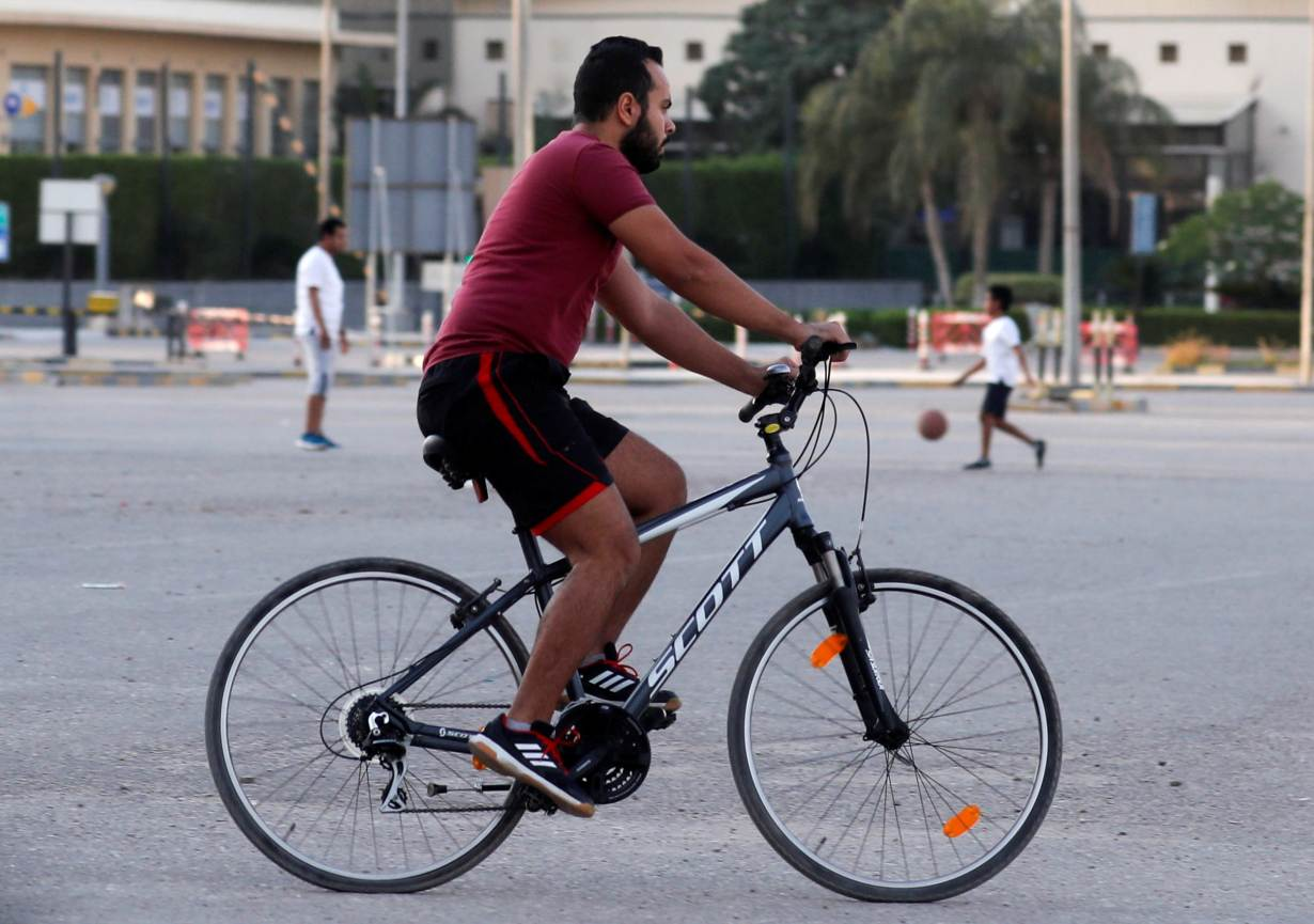 An Egyptian man rides a bicycle and plays with others at an open air area as Egypt closed clubs to slow the spread of the coronavirus disease (COVID-19) before iftar, or breaking fast, during the holy month of Ramadan, in the Cairo suburb of Maadi, Egypt