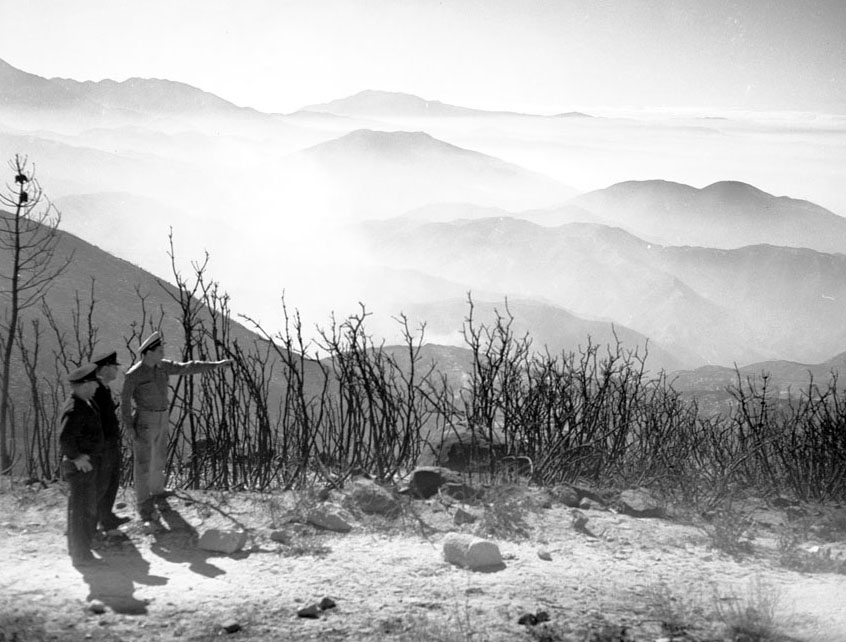 Fire officials observe destruction caused by a wildfire near Lake Arrowhead in 1953. Courtesy of the Los Angeles Examiner Collection, USC Libraries.
