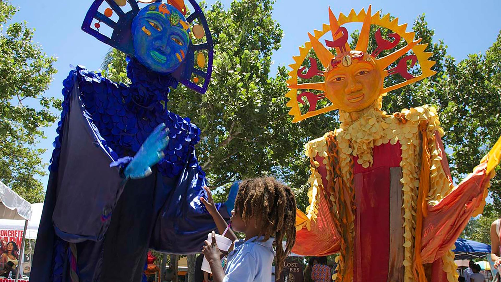 A little boy looks up at two masked figures at the 2017 edition of the Day of the Ancestors: Festival of Masks. | Photo by Sahra Sulaiman, Courtesy of LA Commons