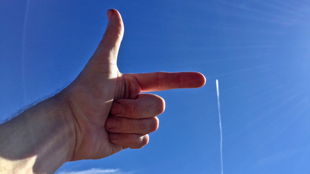 Hand pointing at a contrail | Photo: Stuart Anthony, some rights reserved