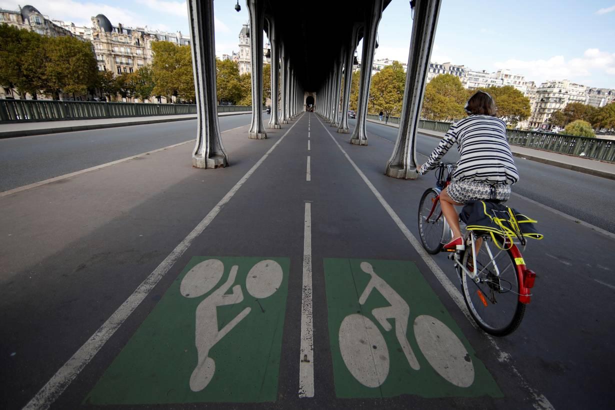 ARCHIVE PHOTO: A woman rides a bicycle along a bike path on the Pont de Bir-Hakeim bridge in Paris, France, September 14, 2018. | REUTERS/Gonzalo Fuentes