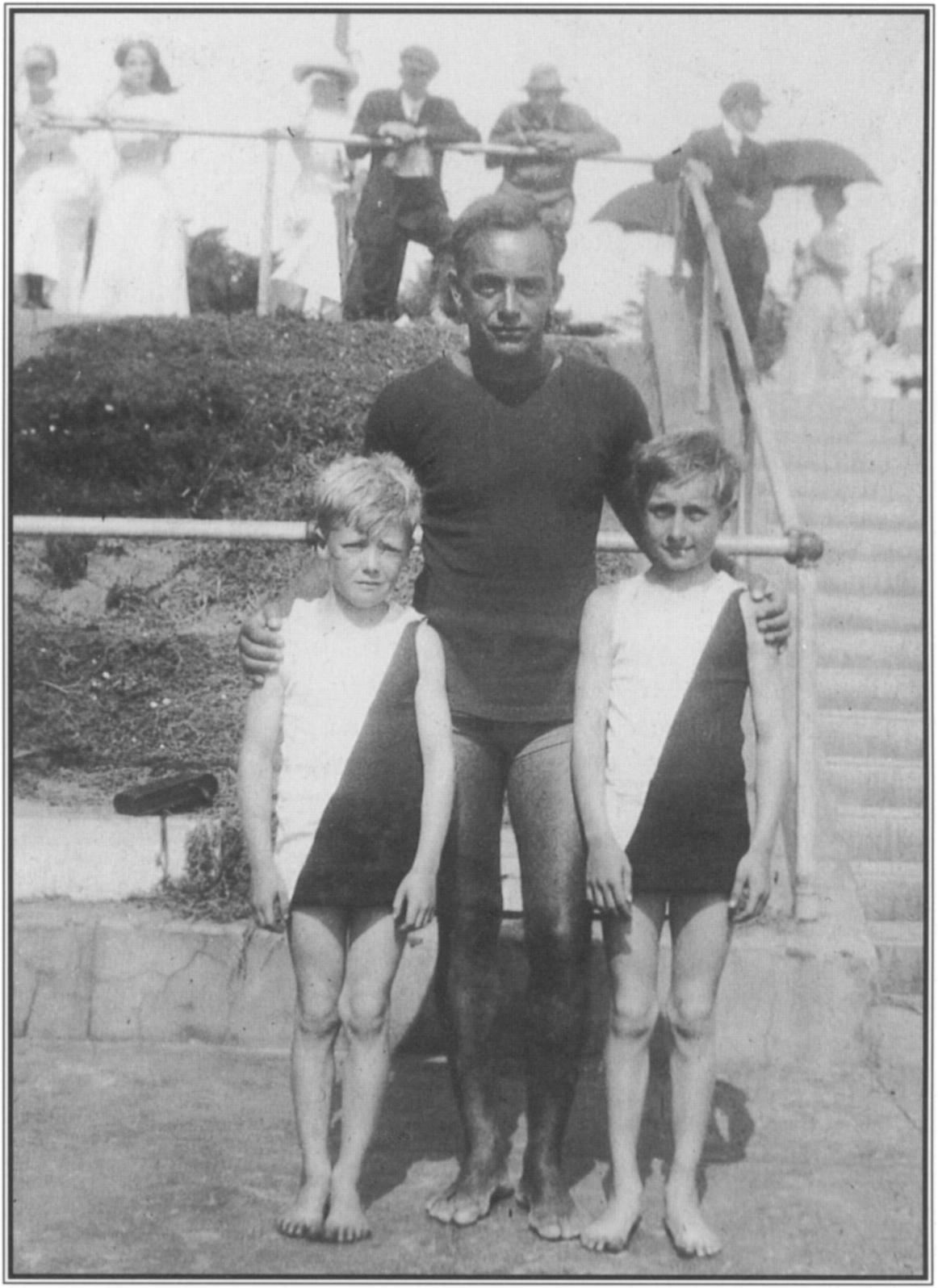At Redondo Beach in 1910, George Freeth posed with two of his star pupils, brothers Tommy and Jerry Witt. Knock-kneed Tommy, on the left, was to become a div­ ing champion; Jerry was a nationally ranked swimmer.