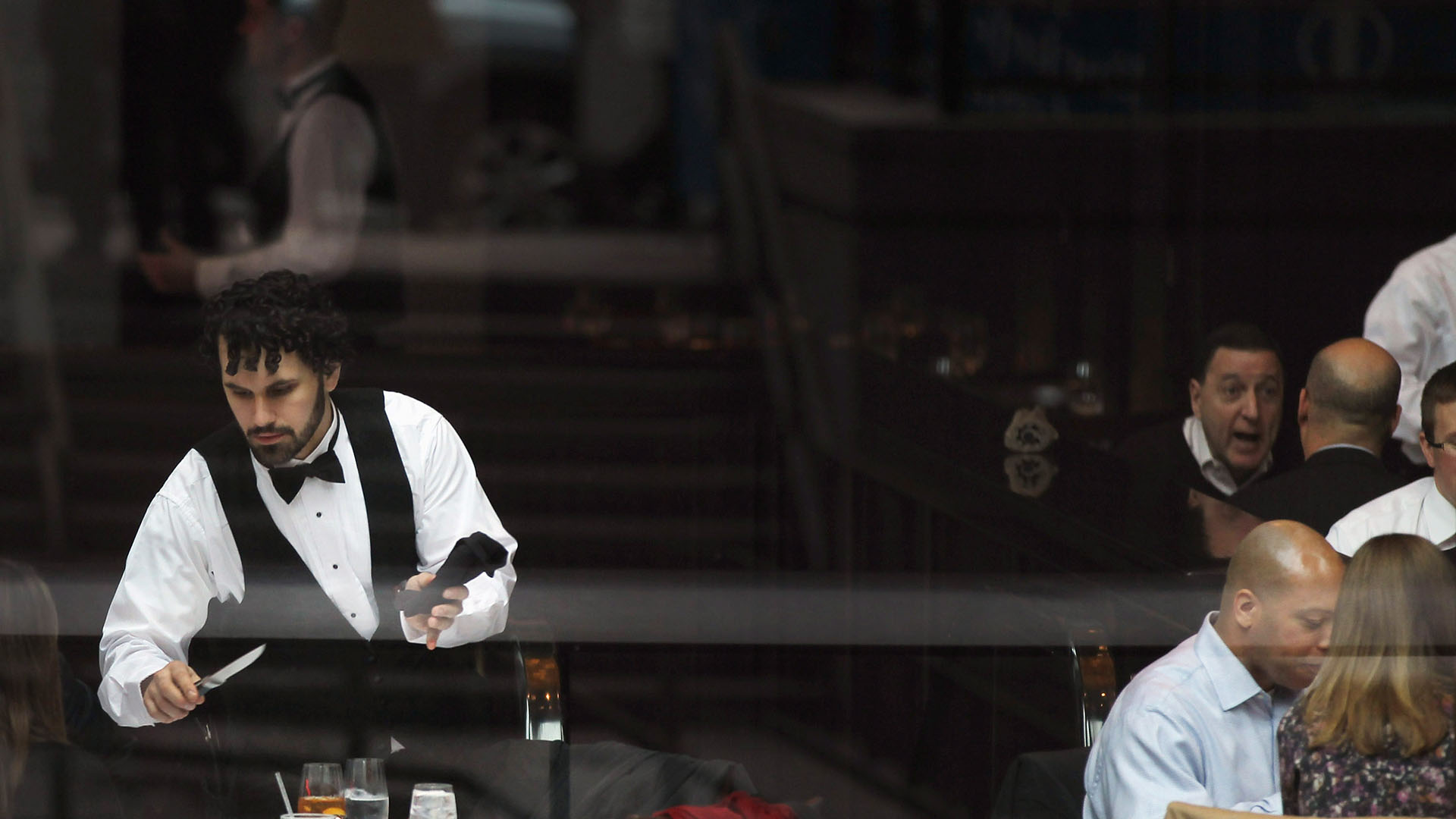 A waiter clears a table at a restaurant popular for business lunches on in New York City. | Spencer Platt/Getty Images