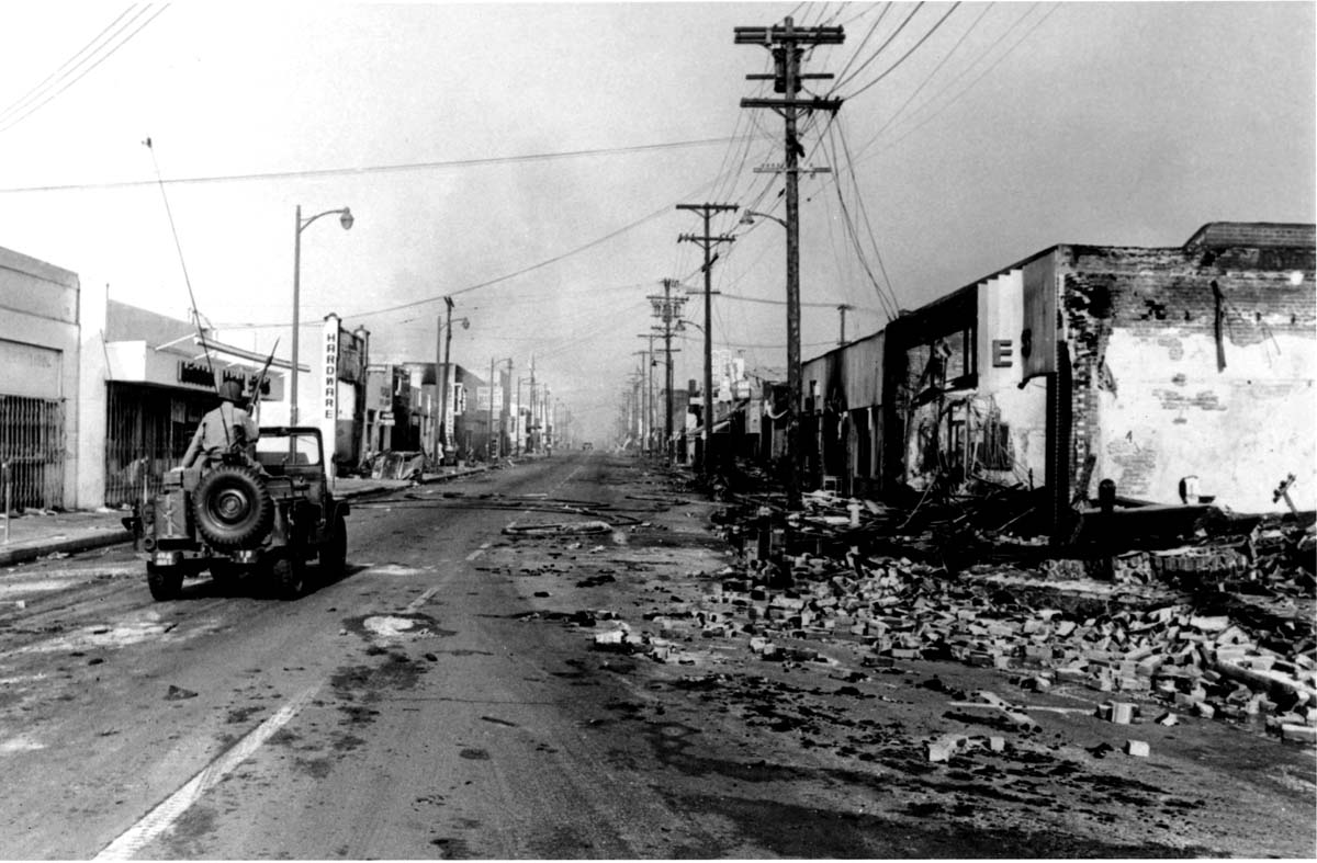 National guardsman in a jeep patrol a rubble-strewn street in the Watts neighborhood after a several-day long riot, Los Angeles, California, mid August, 1965.  PhotoQuest/Getty Images