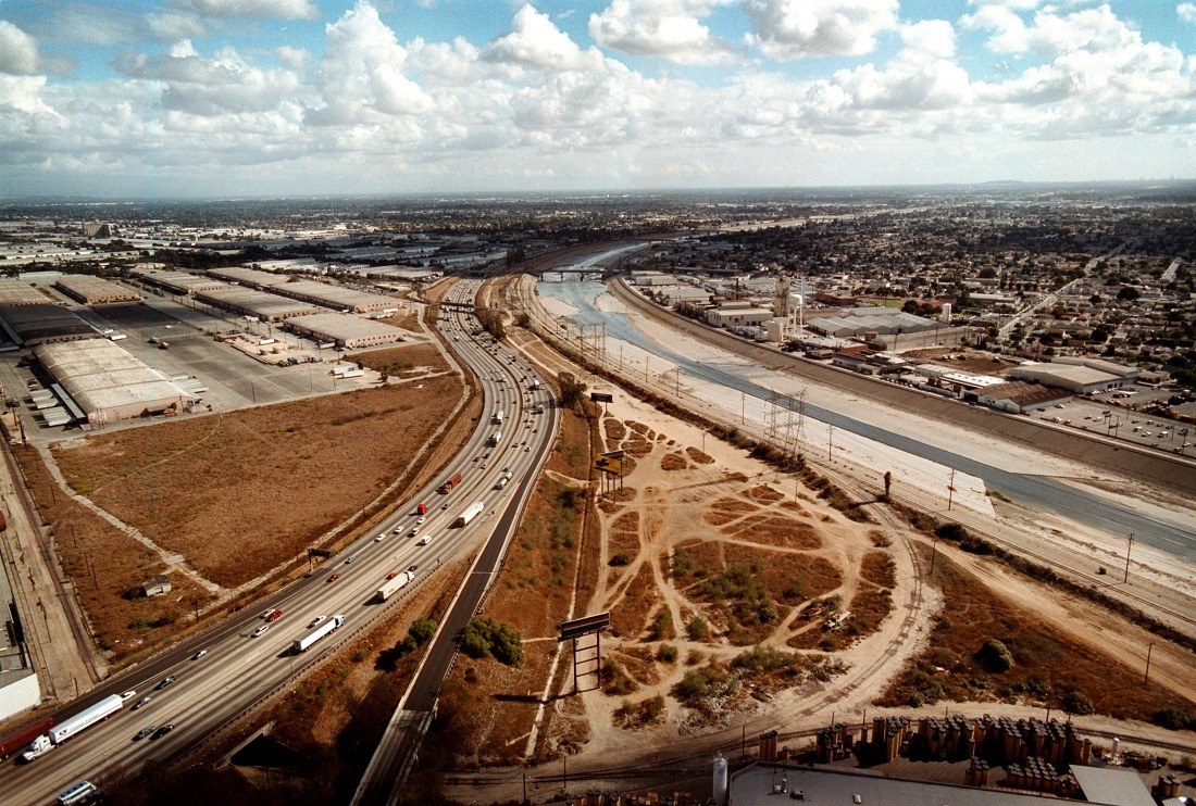 The cement-confined Los Angeles River, right, slides past open industrial lots in Los Angeles, CA