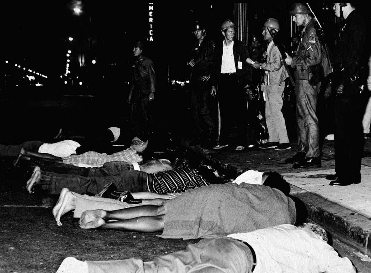 Armed police stand by as rioters lay face down in the street during the Watts race riots, Los Angeles, California, August 1965   Hulton Archive/Getty Images
