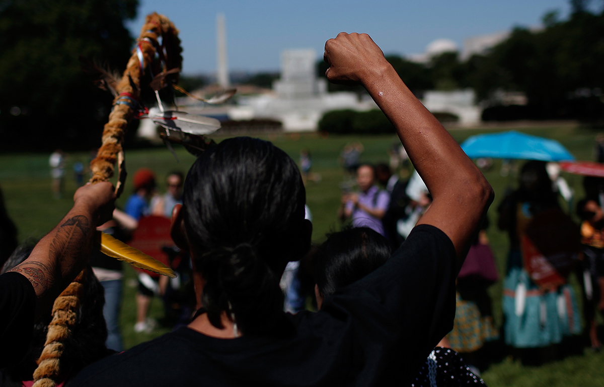"""Members of the the San Carlos Apache Nation attend a protest outside the U.S. Capitol against a land swap that """"threatens the sacred Apache Leap site with environmental damage from nearby high-risk copper."""" July 22, 2015.   Win McNamee/Getty Images"""