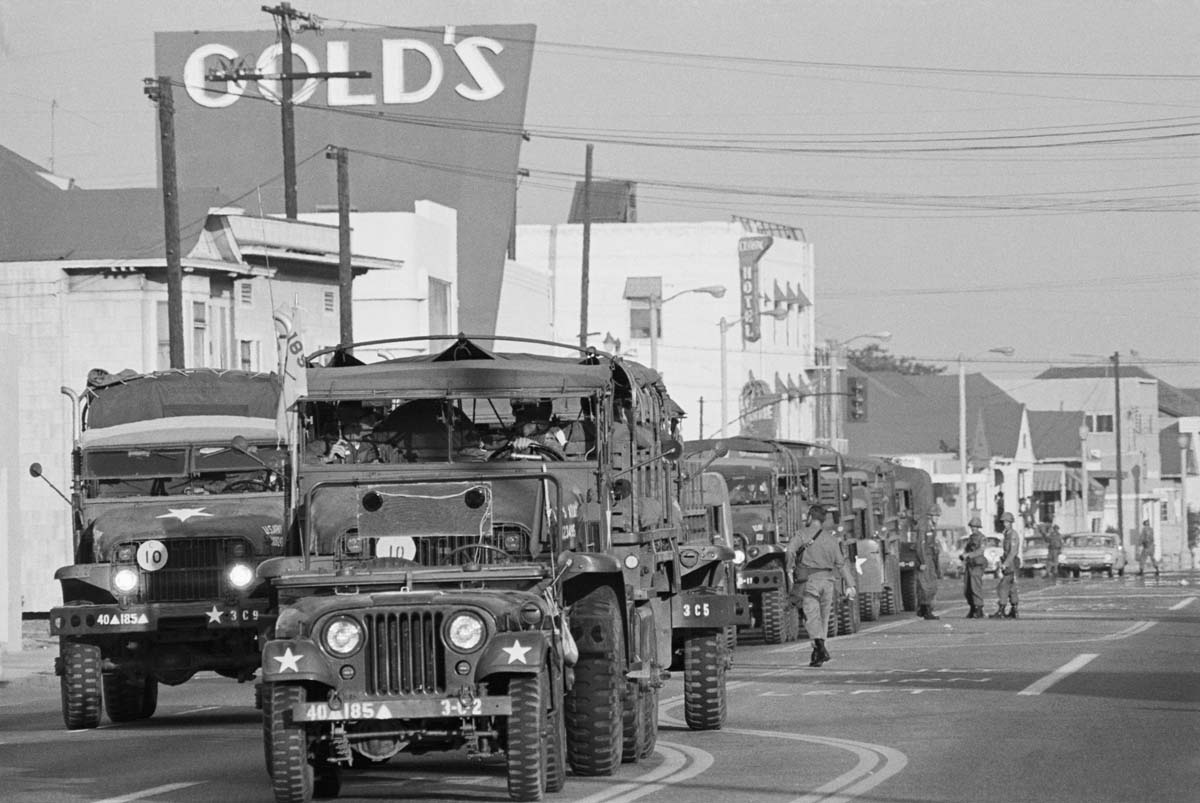 Los Angeles, CA: A convoy of trucks rolls into the Watts district loaded with National Guardsmen ordered in to the area to quell Watts Uprising.   Getty Images