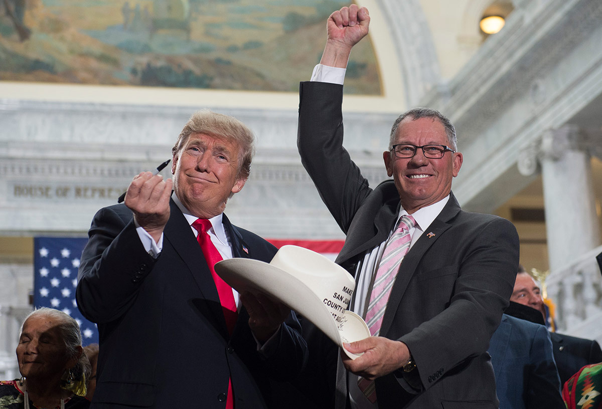 US President Donald Trump holds up a pen after signing the hat of Bruce Adams, Chairman of the San Juan County Commission, after signing a Presidential Proclamation shrinking Bears Ears and Grand Staircase-Escalante national monuments.SAUL LOEB/AFP Getty
