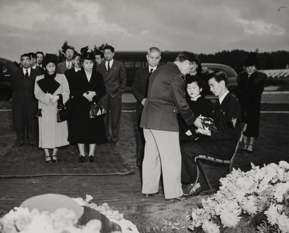 A photograph of a man receiving a condolence flag at Hiroshi Sugiyama's reburial ceremony, 1948 December 15 | Go for Broke National Education Center Collection, USC Libraries
