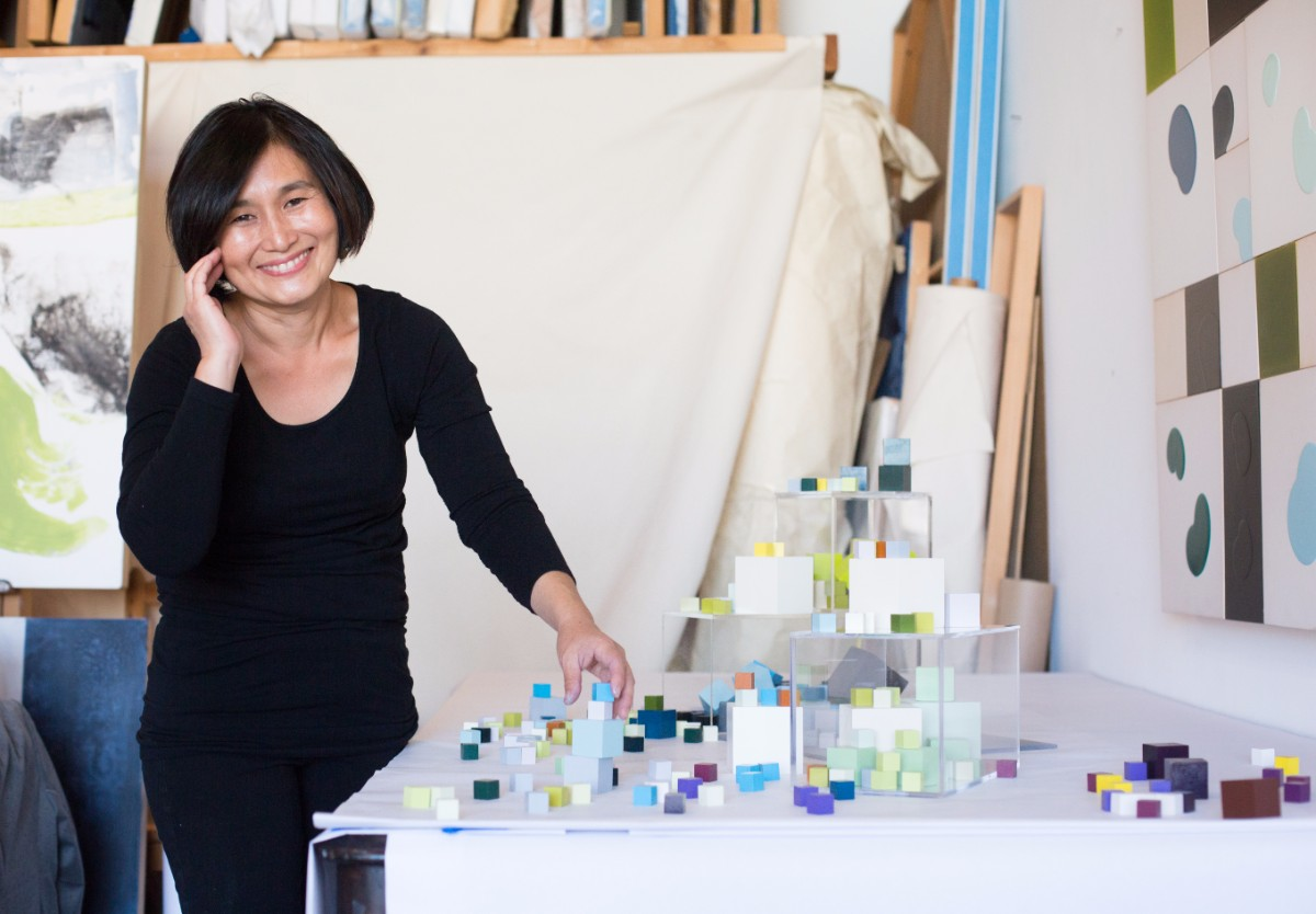 Gina Han arranges the cubes in her installation. | Magali Gauthier Santa Fe Art Colony