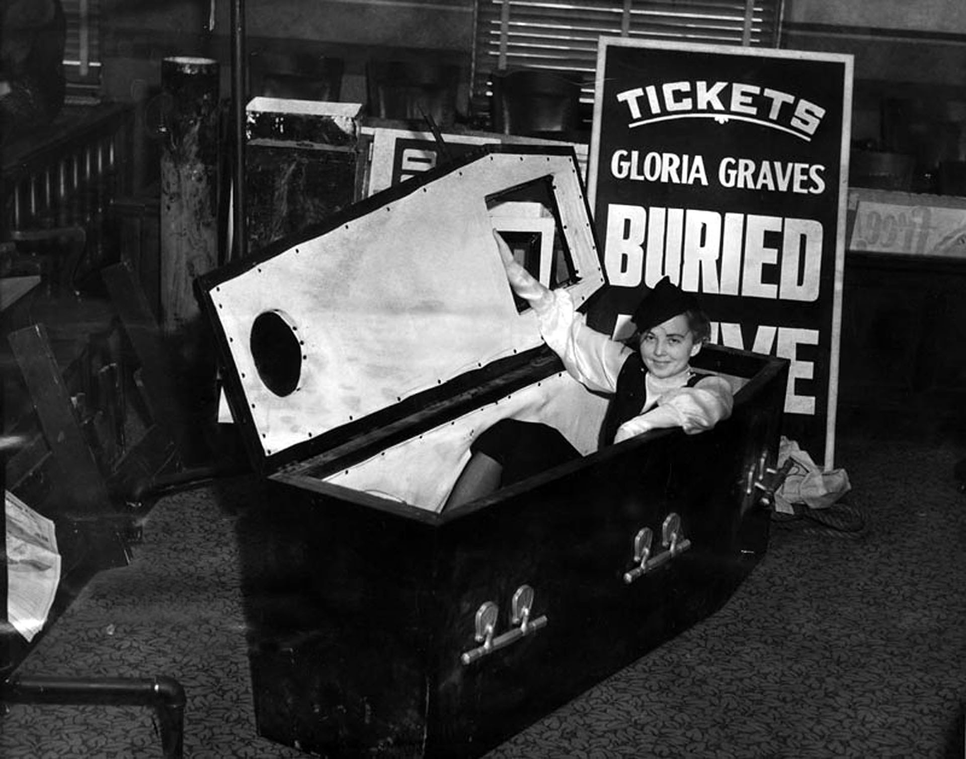 "A girl and her coffin. Gloria Graves, the ""buried alive girl,"" brought her crypt to court to prove she wasn't in violation of a city ordinance. Photograph courtesy of Herald-Examiner Collection, Los Angeles Public Library"