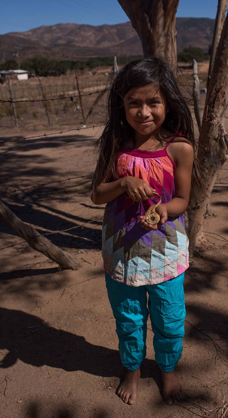 Little girl with a basket necklace she made | Rose Ramirez
