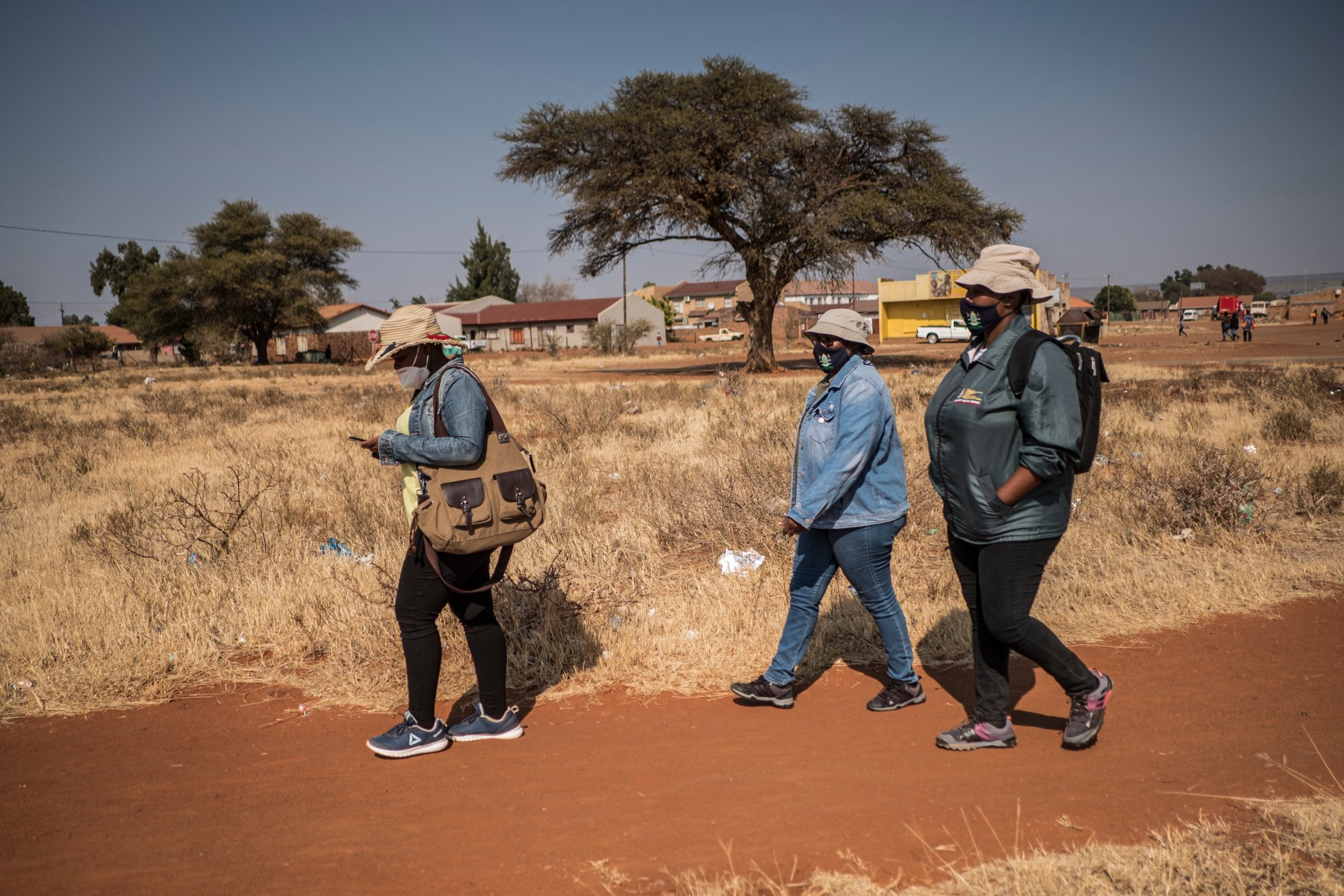 Community Healthcare Workers, Thatayaona Gaebetse (35), Emily Mkenku (55) and Kereng Motlhale (44) walk to homes to do tracing in the community close to the Pudumong Healthcare Centre in the North West Province, South Africa, on Sept. 4, 2020.   TRF