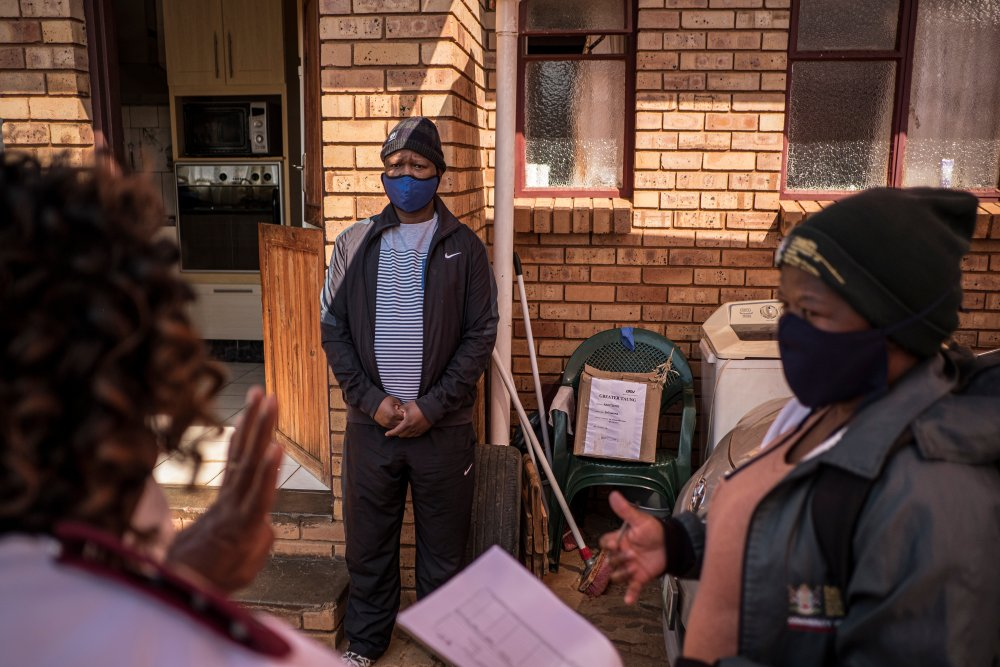 Sister Rachel Asitile (61) (L) and Community Healthcare Worker Patricia Galeboe (36) (far right) do a follow up check on Thuso Kalanyane who tested positive for COVID-19. | Thomson Reuters Foundation/Gulshan Khan