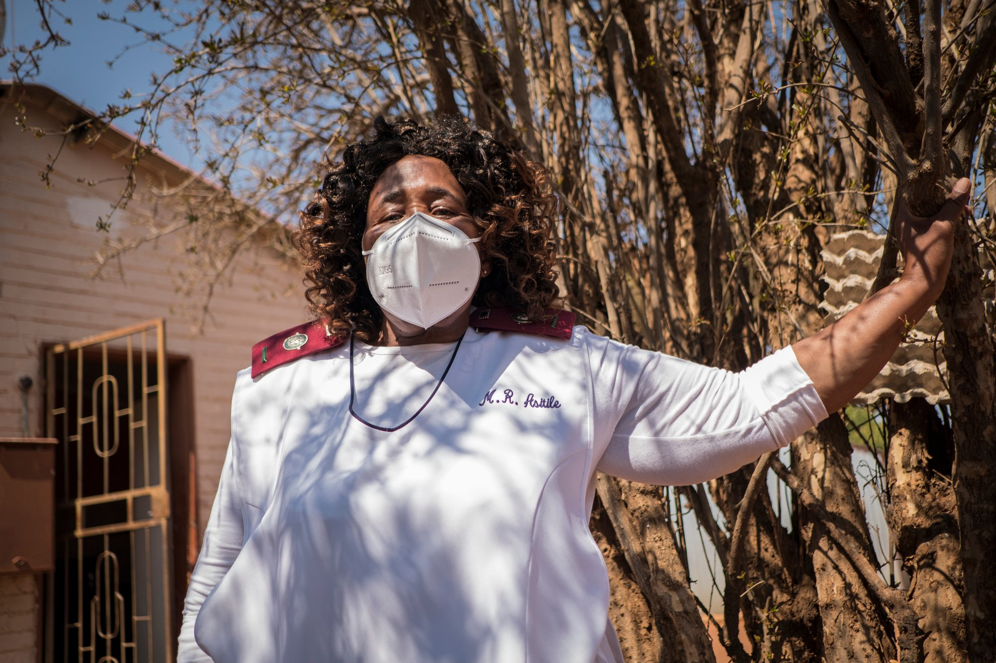 Sister Rachel Asitile (61) stands for a portrait outside the home of a patient who tested positive for COVID-19.   Thomson Reuters Foundation/Gulshan Khan