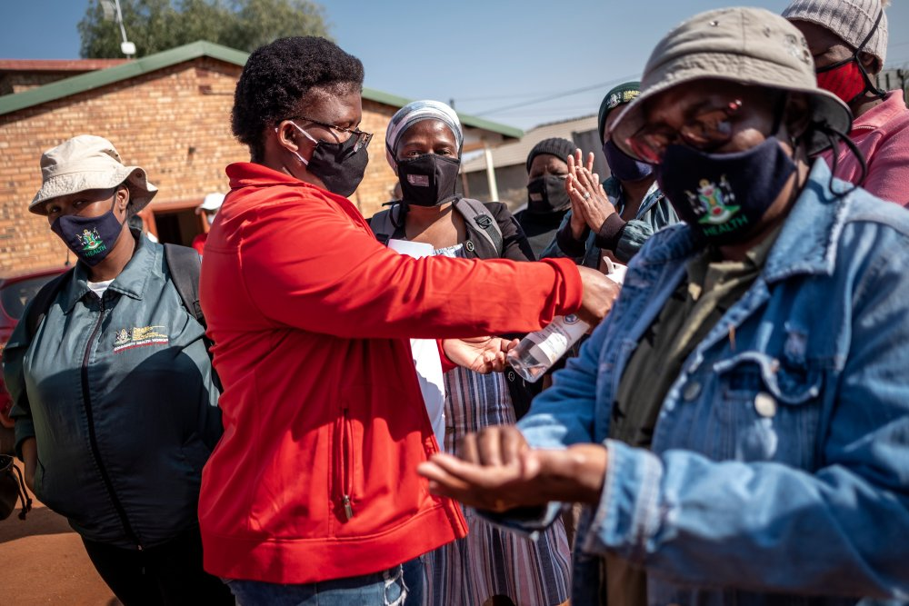Gontlafetse Leinane (45) sprays the last few millilitres of hand sanitizer onto the hands of fellow Community Healthcare workers at Pudumong Healthcare Centre in the North West Province, South Africa, on Sept. 4, 2020.   Thomson Reuters Foundation/Gulsha