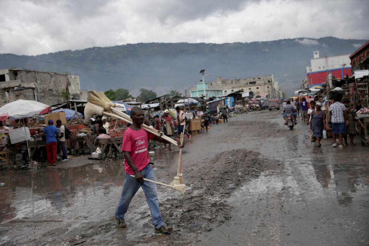 A vendor carrying brooms walks along a street after rains following the passage through Hispaniola island of Tropical Storm Isaias, which became a hurricane afterwards, in Port-au-Prince, Haiti, July 31, 2020. | REUTERS/Andres Martinez Casares