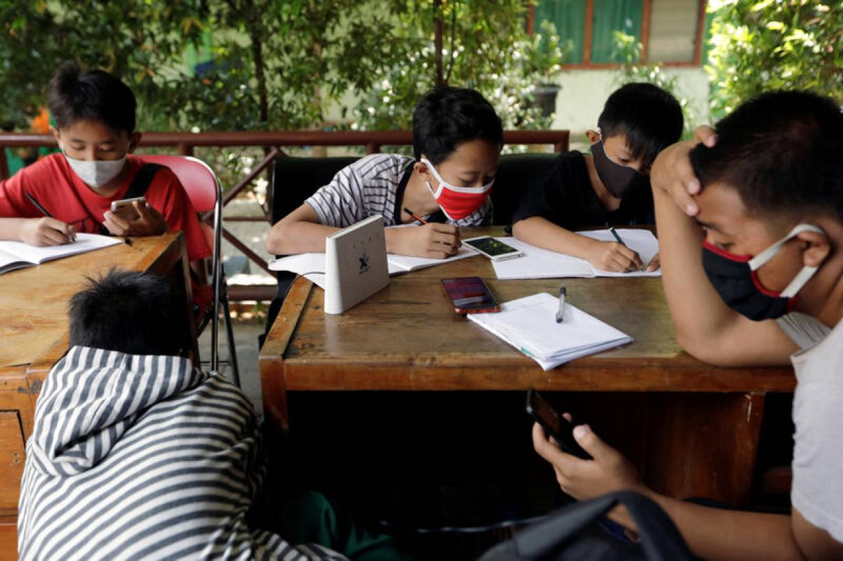 Dimas Anwar Saputra, wearing a red mask, studies with other students using free internet Wi-F access that they got by exchanging plastic waste, amid the coronavirus disease (COVID-19) outbreak,  in Jakarta, Indonesia, September 9, 2020. REUTERS/Willy Kurn