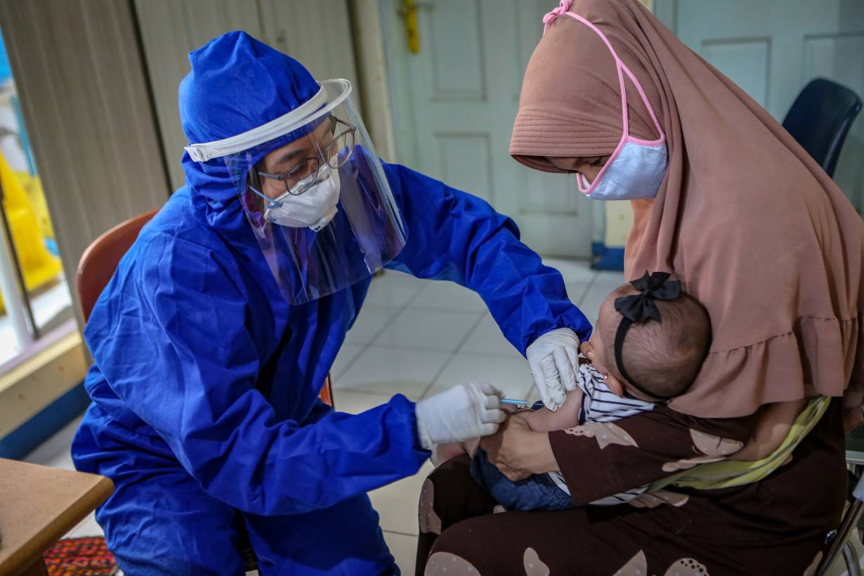 A medical staff member wearing personal protective equipment (PPE) vaccinates a baby, amid the coronavirus disease (COVID-19) outbreak, in Tangerang, near Jakarta, Indonesia May 13, 2020. | Antara Foto/Fauzan/ via REUTERS