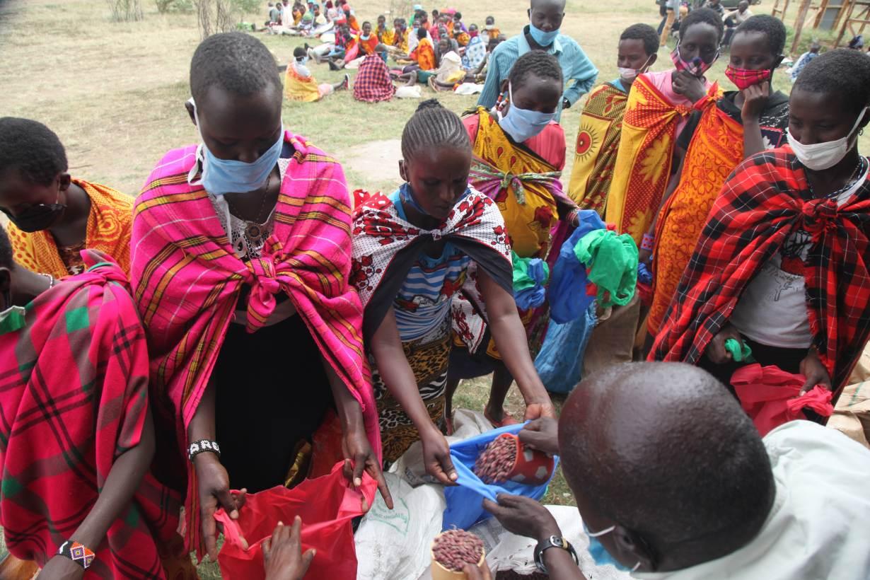Community elders distribute food aid at Nashulai Maasai Conservancy, located near the Maasai Mara National Reserve in Narok county, Kenya on July 14, 2020. | THOMSON REUTERS FOUNDATION/Nita Bhalla