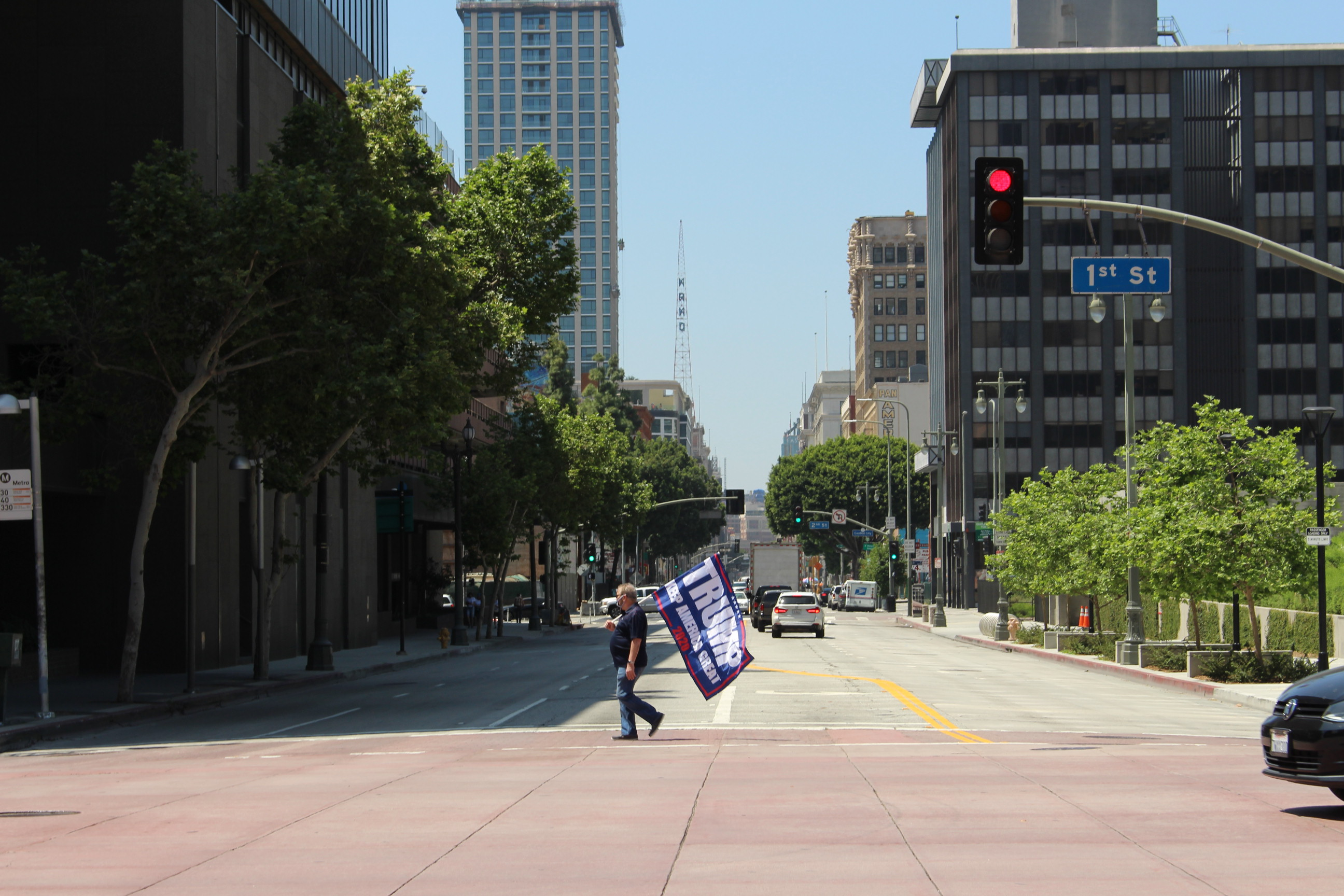 "Man crosses the street in Downtown L.A. with ""Trump 2020"" flag in hand 