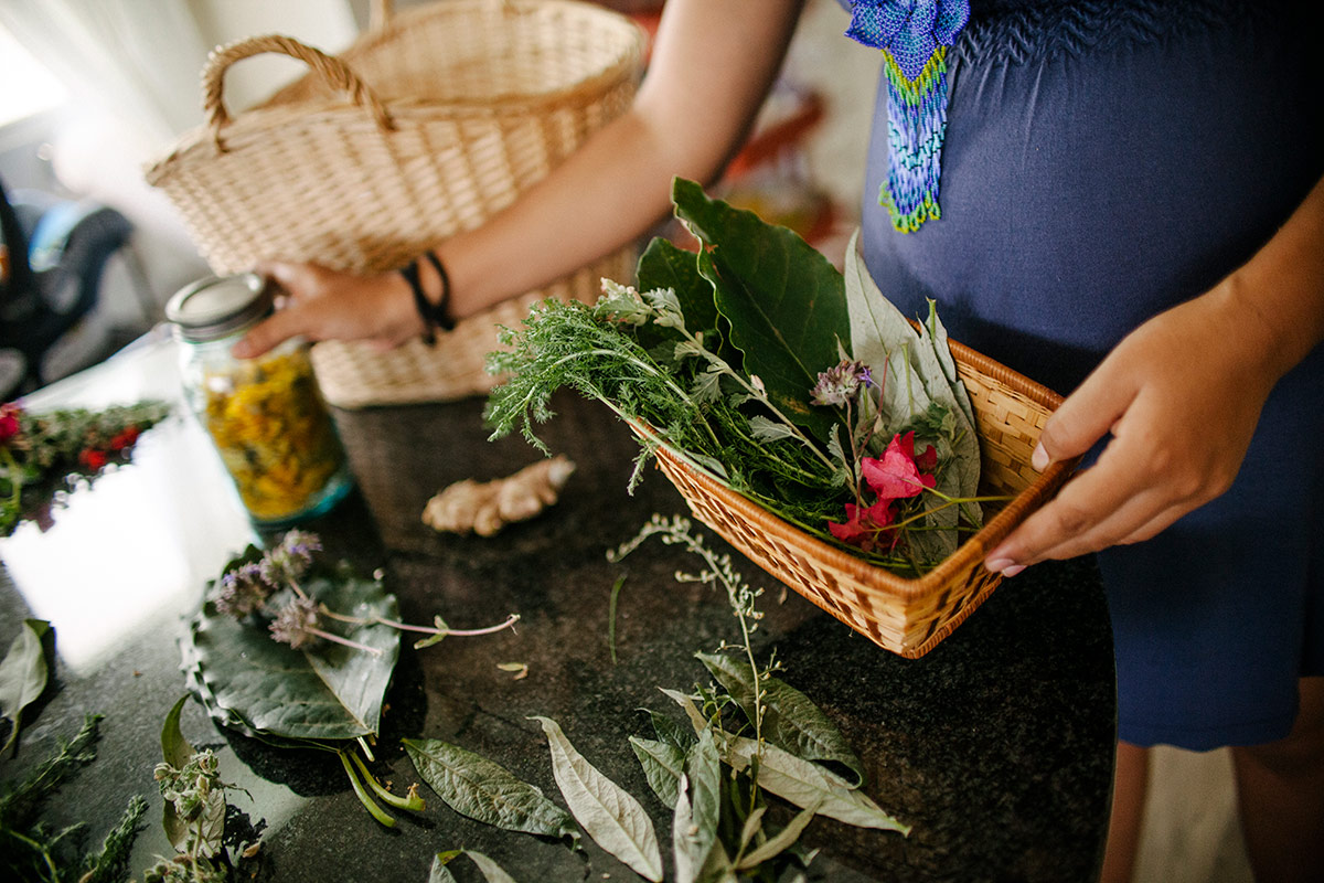 Panquetzani arranges flowers and herbs on a table. | Samanta Helou Hernandez
