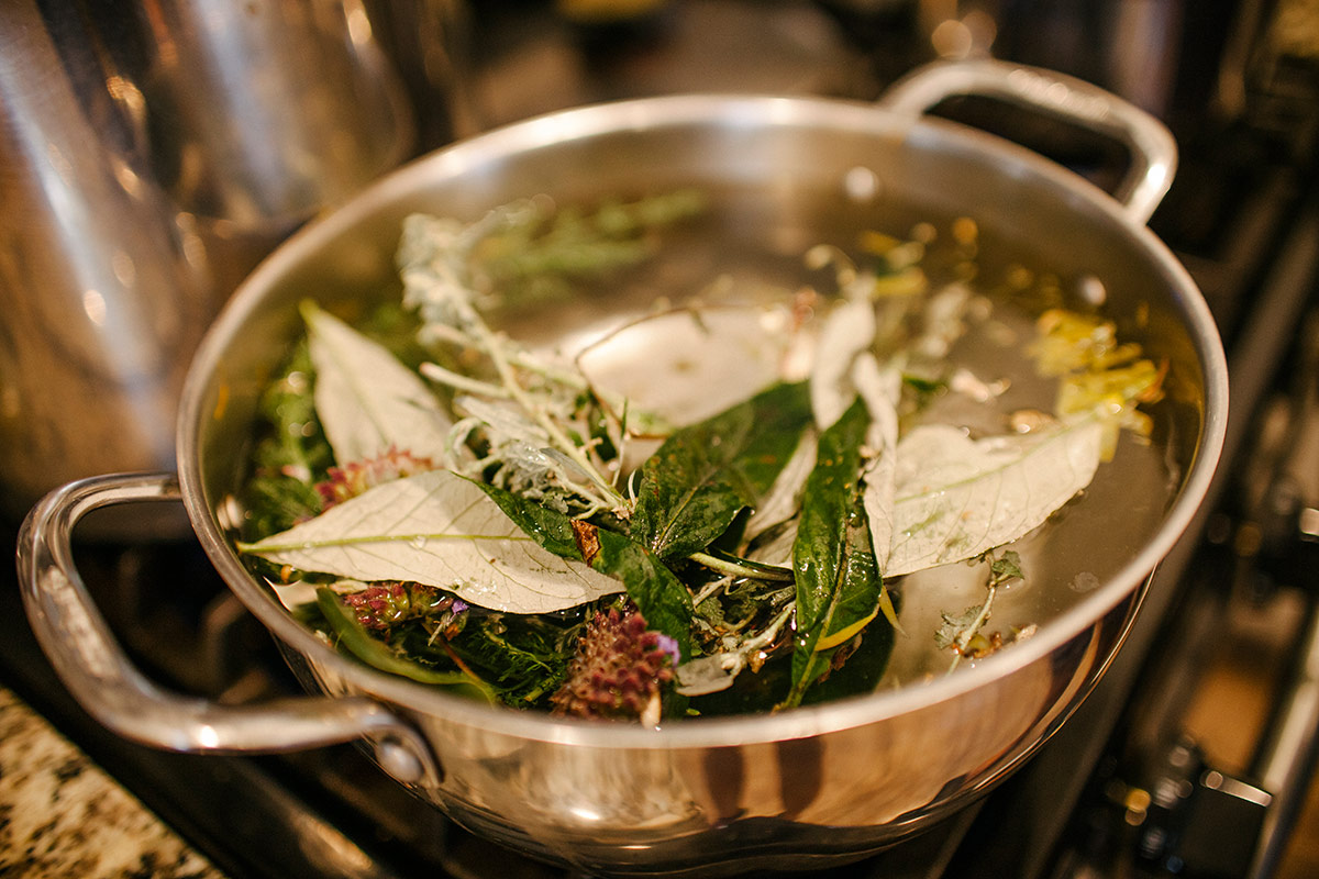 Avocado leaves, mugwort, yarrow, mint, and bougainvillea flowers, all from Panquetzani's garden, boil on the stove to be used as a tea and vaginal steam. | Samanta Helou Hernandez