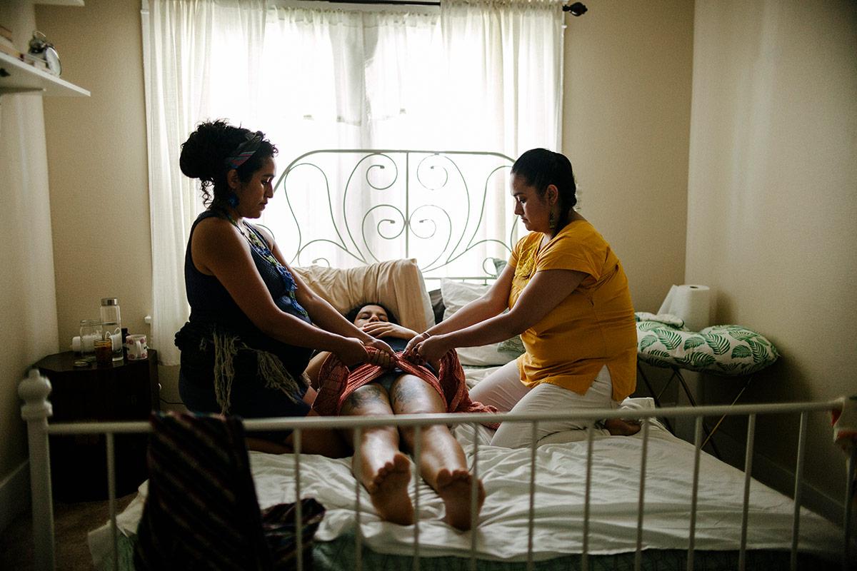 Panquetzani and her apprentice tie a rebozo around Kat Cardenas' pelvis. | Samanta Helou Hernandez