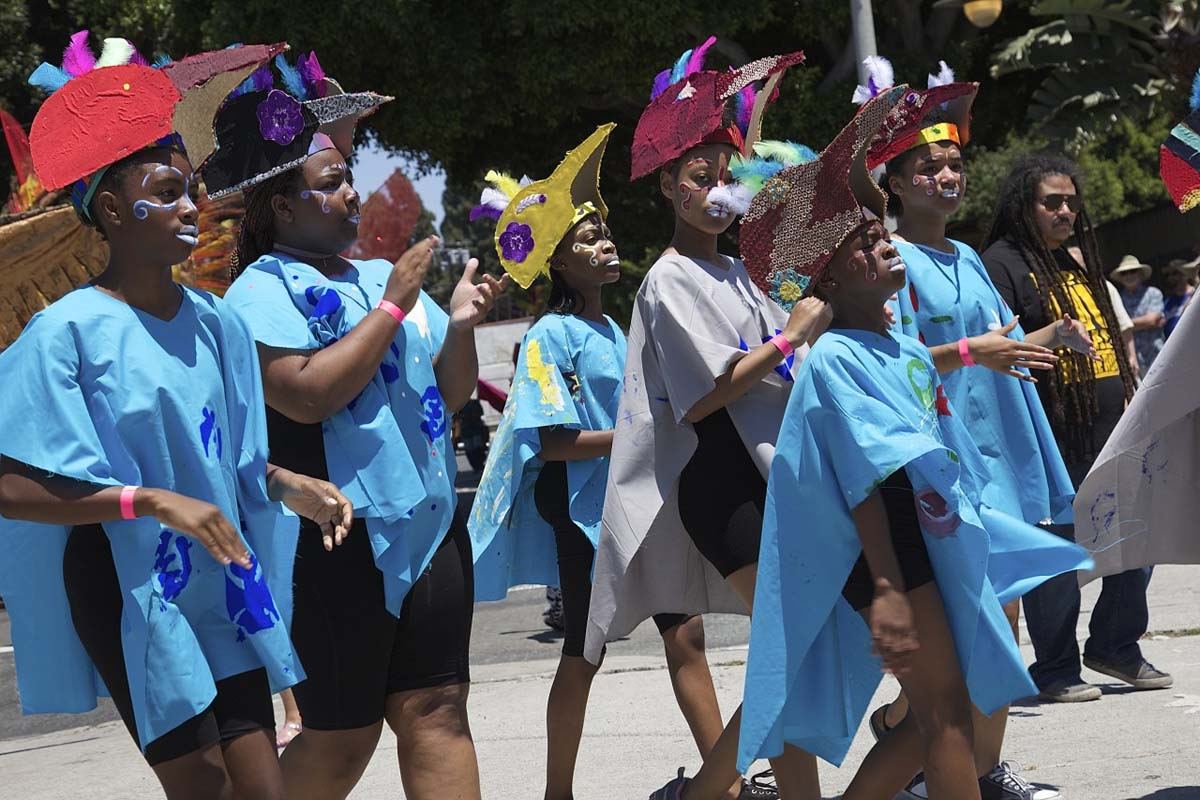 Young people wearing blue tunics and colorful helmets walk at the 2017 edition of the Day of the Ancestors: Festival of Masks. | Photo by Sahra Sulaiman, Courtesy of LA Commons