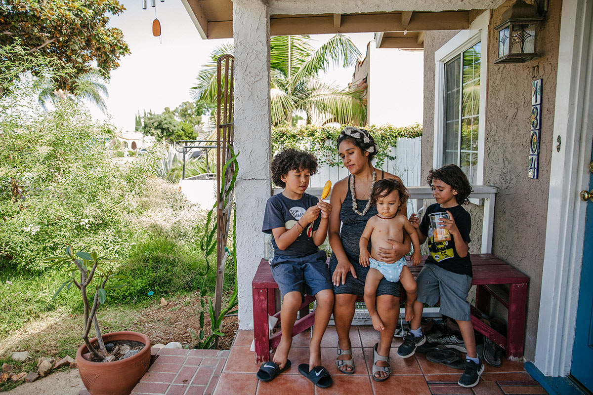 Panquetzani sits with her children on a porch. | Samanta Helou Hernandez