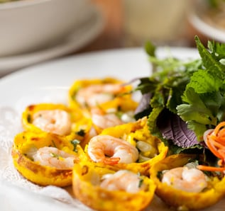 Banh Khot,  crispy rice cakes filled with whole shrimp, mung bean & scallions, flavored with a dash of turmeric and served with Asian greens and lime chili fish sauce | Courtesy of Brodard