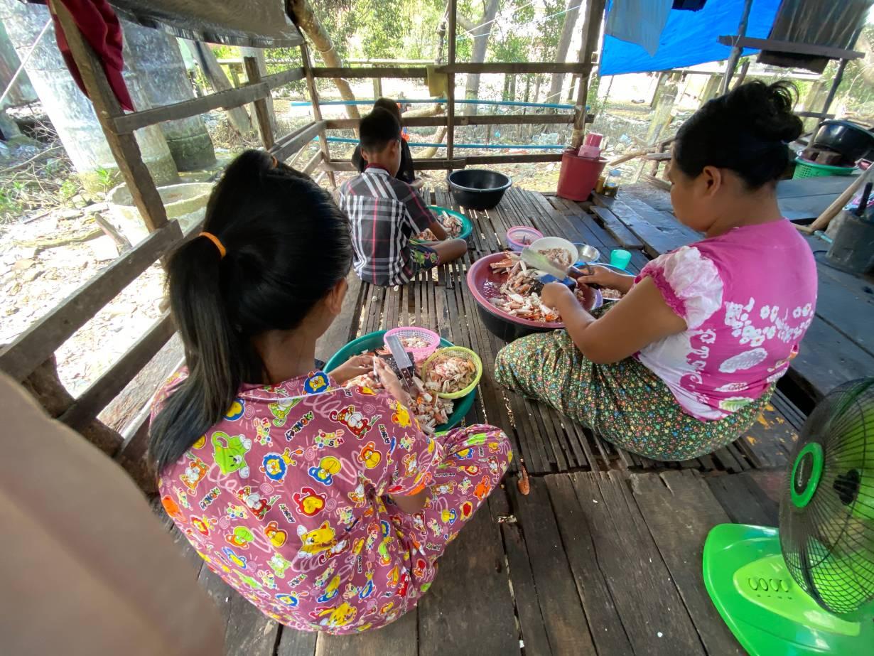 Burmese children help their parents peel crabs at their home in Ranong, Thailand on September 10, 2020. | Thomson Reuters Foundation/Nanchanok Wongsamuth